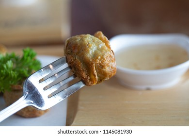 Jock fried chicken in front of blur a small cup sauce. Chicken cho ball shaped  skewer by fork. Close up and selective focus.