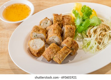 Jock Fried Chicken meat filled in bean curd sheet in a white dish on wood table background for a snack ready to serve.