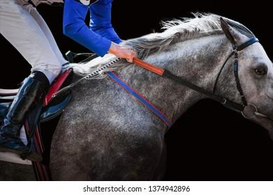 jockey on arabian horse during the race detail closeup isolated on black