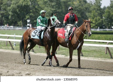 Jockey on his Race Horse being warmed up by Pony Boy