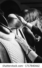 Jockey saddle up the thoroughbred horse for dressage or equestrian race. Close-up of hands on saddle and mane. Noble aesthetics, dress code, professional equipment, competition and excitement concept