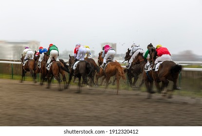 Jockeys on their horses running towards finish line in race course.