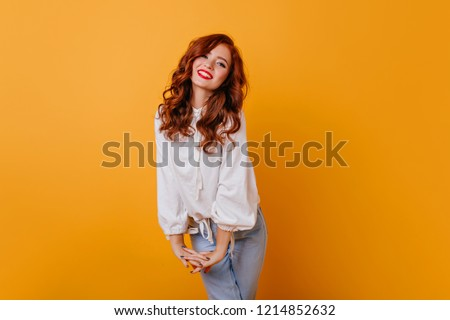 560a5dc157ea Jocund caucasin lady smiling on orange background. Indoor photo of refined  curly woman in elegant