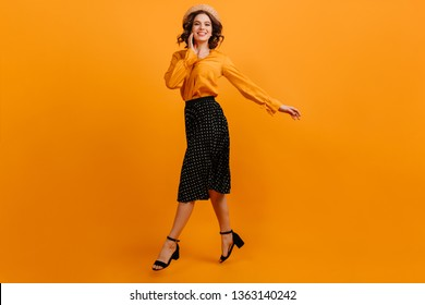 Jocund girl in straw hat jumping on yellow background. Studio shot of blithesome woman dancing with smile.