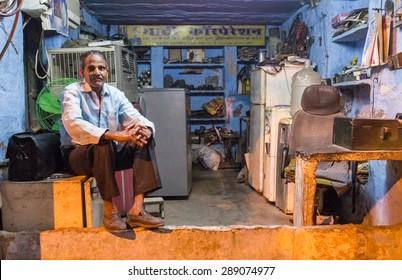 JODHPUR, INDIA - 10 FEBRUARY 2015: Elderly electrician sits on fridge before closing refrigerator service shop.