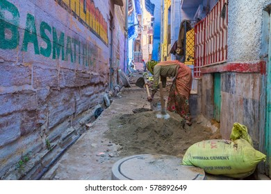 Jodhpur, India 16th January 2017 - A woman mixes cement for construction in a sidestreet in the blue city of Jodhpur, India