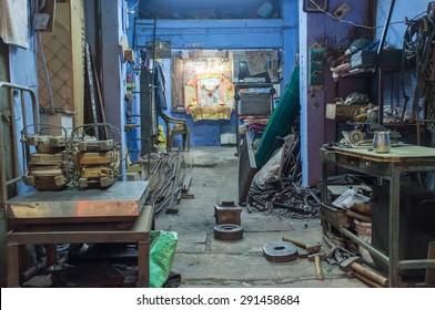 JODHPUR, INDIA - 17 FEBRUARY 2015: Empty mechanics shop with small shiva temple in background.