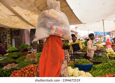 Jodhpur/ India 18 March 2019 Rural indian woman carrying luggage on head stand in the sardar vegetables market on the street at Jodhpur city Rajasthan India