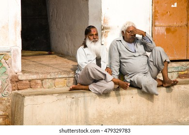 Jodhpur, India - 2015, January 1 : Two indian men sitting in the courtyard of a Hinduist temple in the town of Jodhpur, Rajasthan, India