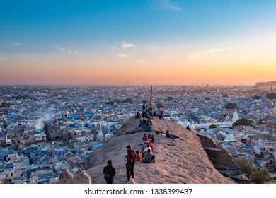 Jodhpur, India - December 30, 2018 : Tourists sitting and standing at top of the hill to see Jodhpur, the Blue City, Rajasthan, India