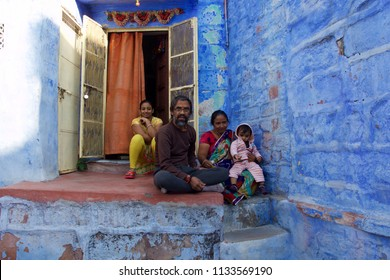 JODHPUR, INDIA - JANUARY 2018: Indian family with small baby sitting outside their house in Jodhpur the blue city of Rajasthan.