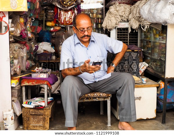 Jodhpur, India - June 2,2018 Illustrative Editorial. Indian Man in Blue Shirt with Gray Pants Looking for Him Smartphone at Him Store in Jodhpur Market.