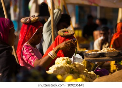 Jodhpur, India - November 29, 2009: Indian women dressed in traditional saris and head ring cushions buy vegetables at local market day to carry home balanced on their heads