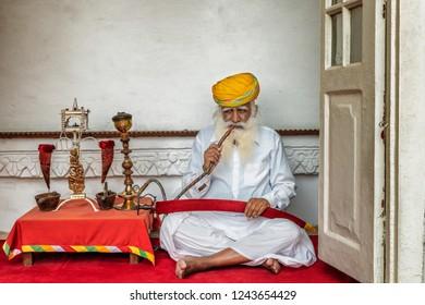 Jodhpur, India - October 14, 2018: Old man smoking water pipe, Jodhpur, Rajasthan, India