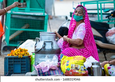 Jodhpur, Rajashtbn, India. 30 March 2020. Old woman wearing protective mask selling food on road due to lock down, new strain of Coronavirus is deadly, second wave of COVID-19 outbreak in india.