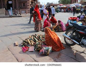 Jodhpur, Rajastan, India – February 19 2019: Women sell Indian goods (belts, saris, bags) on land at the Sardar market in Jodhpur