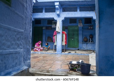 Jodhpur, Rajasthan, India - August 16, 2012. A woman with her daughter are seen at the yard of a blue house, at the city of Jodhpur, at the state of Rajasthan in northwestern India.