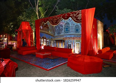 Jodhpur, Rajasthan, India, August 20th, 2020: Beautifully decorated red sofas or couch ready for the guests sitting at a wedding ceremony in backyard, night ceremony venue, wedding event concept