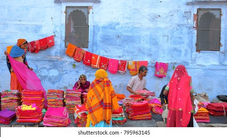 JODHPUR, RAJASTHAN, INDIA - DECEMBER 16, 2017: Colorful scenery at the market near Sardar Market with colorful fabric, women dressed with saris and blue walls in the background