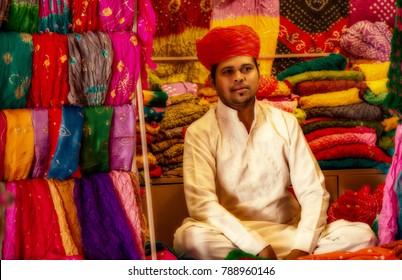 Jodhpur, Rajasthan, India, December 16,2017: Young Rajasthani male wearing traditional dress selling Rajasthan dress materials at Mehrangarh Fort, Jodhpur.
