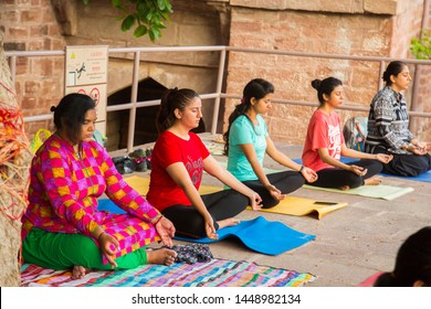 Jodhpur, rajasthan, india - July 7th, 2019: fitness, yoga and healthy lifestyle concept, Mature healthy people doing yoga. Group of multiethnic people exercising together.