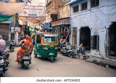 JODHPUR, RAJASTHAN, INDIA  - MARCH 04, 2016: Wide angle picture of tuk tuk, motorcycle and people in their daily life in old Jodhpur, the blue city of Rajasthan in India.