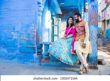 Jodhpur, rajasthan, india - may 18th, 2018:  indian couple sitting together wearing traditional ethnic dress looking at each other happily before wedding day in blue house in the background, city