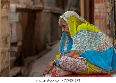 Jodhpur,India-November 2, 2107: Traditionally dressed unidentified old indian woman sits in front of her house,