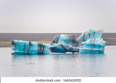 Joekulsarlon Glacier Lagoon tiefblauer Eisberg mit dunklen Schichten vulkanischer Asche, die sich regelmäßig Muster bilden