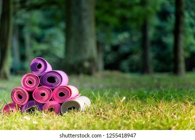 joga mats stacked together on the green grass in public park