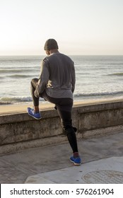 A jogger does some stretch exercises next to the road, overlooking the ocean, after an early morning run.