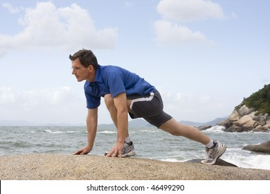 Jogger doing fitness exercises on a rock at the sea