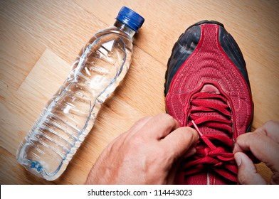 Jogger at home, tying his sneakers with a water bottle nearby