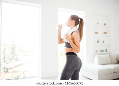 Jogger run runner energy sweaty yoga vitality wellness concept. Side profile view photo portrait of sexual attractive beautiful glad sportive woman holding bottle in hand standing in white room