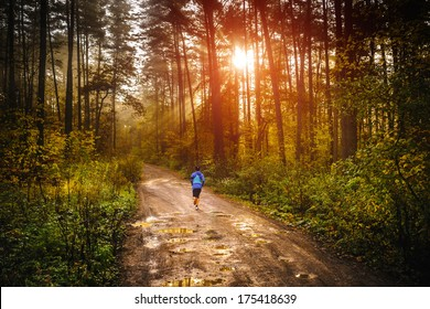 Jogger running a muddy path in autumn forrest with sun rising up