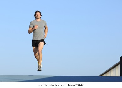 Jogger running towards camera on blue with the horizon in the background