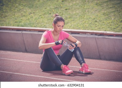 Jogger sitting on running track and holding bottle of water