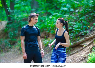 Jogging active couple resting after running outdoors in forest