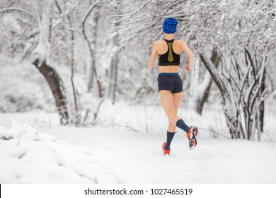 Jogging in any weather. Young hot runner woman running in winter park in snow weather