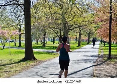 Jogging and biking on Boston Esplanade during spring day