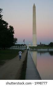 Jogging by reflecting pool at dusk