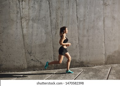 Jogging, endurance and sport concept. Side shot fit sporty young woman in activewear running near concrete wall into sun, daily training and morning exercises, sportswoman training to run marathon