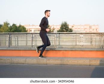 Jogging Healthy Looking Young Man Cross Bridge Under Morning Sunlight