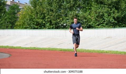 Jogging man on the stadium. Horizontal shot