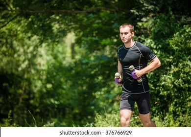 Jogging in nature - young man training with barbells