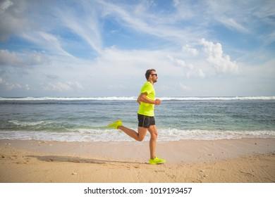 Jogging on a tropical sandy beach near sea / ocean.