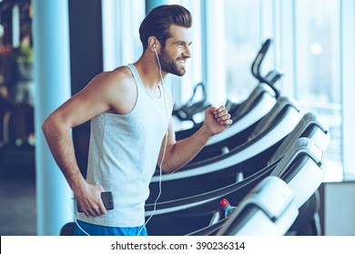 Jogging with pleasure. Side view of young handsome man in headphones looking away with smile while running on treadmill at gym