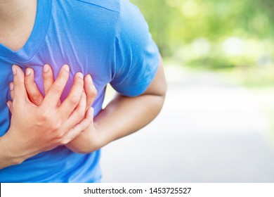 Jogging running athlete man having chest pain while exercising heart attack outdoor Heavy exercise causes the body to shock heart disease. health care concept. Highlighting the red color, showing pain