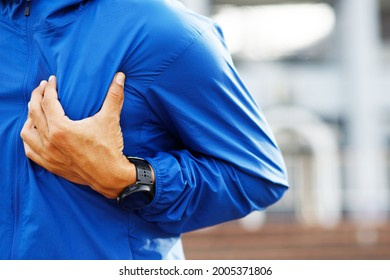 Jogging running athlete man having chest pain while exercising - heart attack outdoor. or Heavy exercise causes the body to shock heart disease. may cause life-threatening. health care concept.
