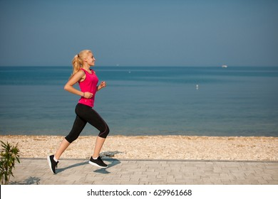 jogging in th beach - woman runns near sea on early summer morning